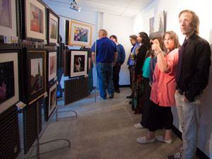 Members of the general public admiring the work of our Photography Beyond the Basics class at a gallery art show